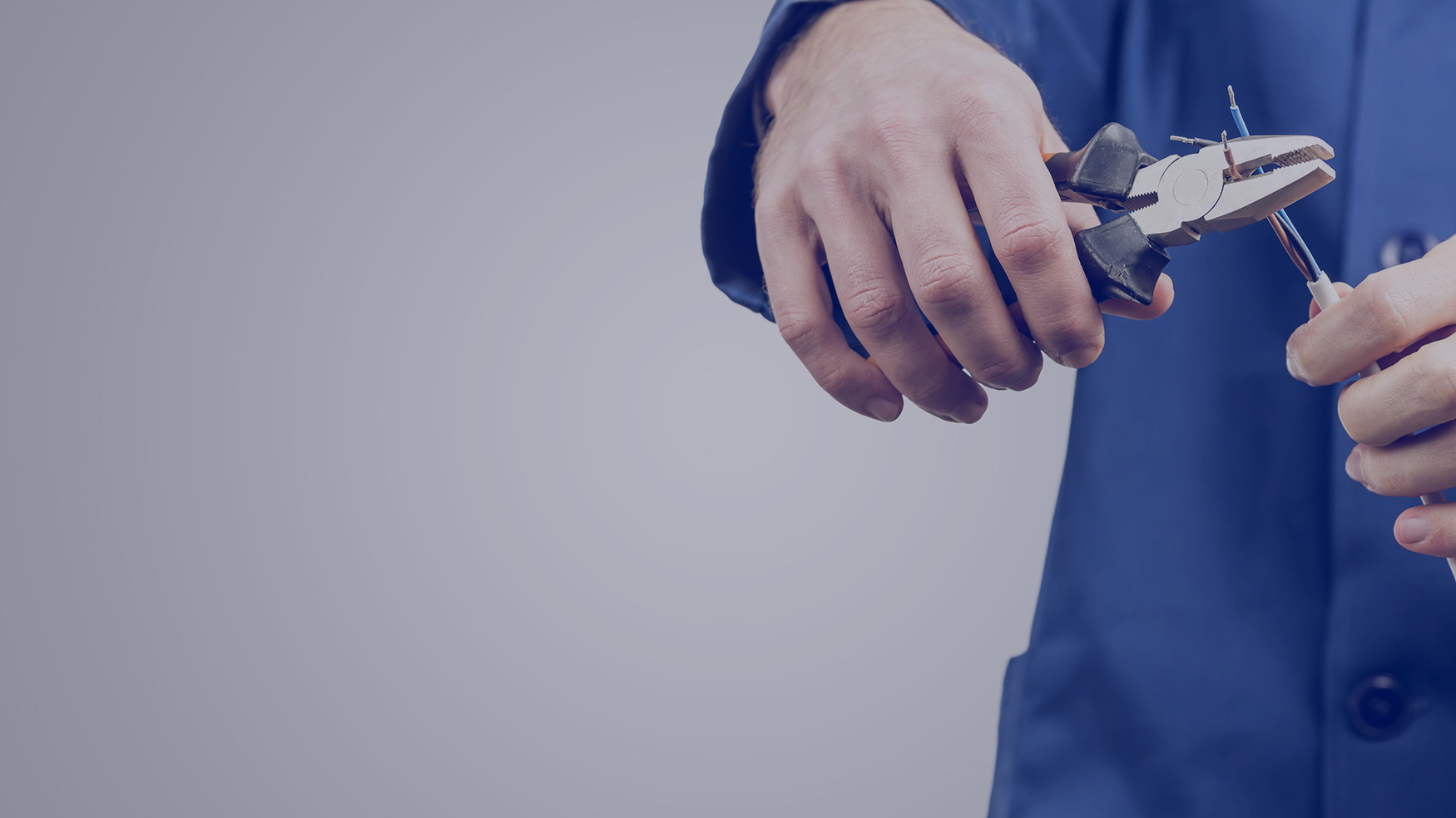 Workman or electrician repairing an electrical cable with a pair of pliers to restore supply to the house, close up view of his hands in blue overalls on grey with copyspace